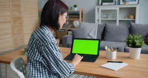 Smiling girl using laptop with green screen working with computer at home. Smiling girl is using laptop with green screen working with computer at home sitting stock video