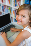 Smiling girl using laptop in school library Royalty Free Stock Photos