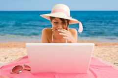 Smiling girl using laptop at the sea. Smiling girl wearing bikini and straw hat using laptop at the sea stock images