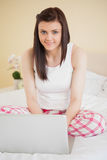 Smiling girl using a laptop sitting on her bed looking at camera Stock Photo