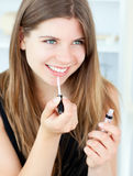 Smiling girl using lipstick Stock Photography