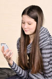 Smiling girl using a mobile phone. Smiling teen girl sitting and looking at mobile phone. photo taken on a light background vertical Royalty Free Stock Images