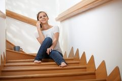 Smiling girl using mobile sitting on stairs Royalty Free Stock Photo