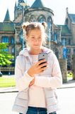 Smiling girl using mobile smartphone in Glasgow historical place. Smiling young beautiful girl using mobile smartphone in Glasgow historical place. Traveling Stock Images