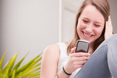 Smiling girl using a phone Stock Images