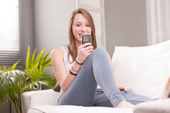 Smiling girl using a phone Stock Image