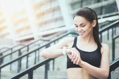 Smiling girl using a smart watch near the stadium Royalty Free Stock Photography