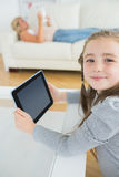 Smiling girl using tablet computer while mother is reading newspaper Royalty Free Stock Images