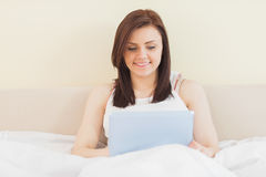Smiling girl using a tablet pc lying on a bed Stock Images