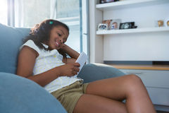 Smiling girl using tablet while sitting on armchair. In living room at home Stock Image
