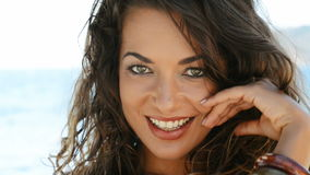 Smiling girl in vacation. Portrait of smiling brunette girl looking at camera at seaside. Happy young carefree woman relaxing and looking at camera in summer stock video footage