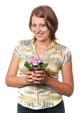 Smiling girl with violets in a flowerpot Royalty Free Stock Photos