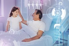 Smiling girl visiting her father in hospital and making him feel happy stock photography