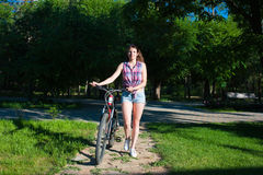 Smiling girl walking with her bicycle Royalty Free Stock Photos