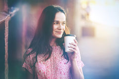 Smiling girl walking with morning coffee stock images