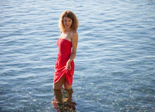 Smiling girl walking near the seashore in the water Stock Image