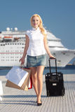 Smiling girl walking on pier. Smiling girl walking on a pier with a cruise ship behind her. She is carrying shopping bags and luggage Stock Images