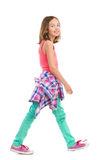 Smiling girl walking, side view. Royalty Free Stock Image