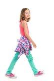 Smiling girl walking, side view. Royalty Free Stock Image