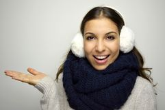 Smiling girl in warm clothing showing product. Beautiful young woman with cold wearing earmuffs, scraf and sweater holding out her. Hand, presenting your Royalty Free Stock Photos