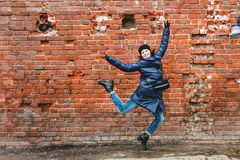 Smiling girl was photographed in a jump on a brick wall background stock images