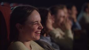 Woman face watching funny movie at cinema. Cinema people watching comedy movie. Smiling girl watching theater performance and laughing. Spectators have fun stock video footage