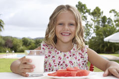 Smiling Girl With Watermelon And Glass Of Milk Outdoors Stock Image