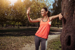 Smiling girl waving to someone in the park after training Royalty Free Stock Photography
