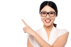 Smiling girl wearing eyglasses pointing away Stock Photography