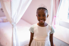 Smiling girl wearing fairy costume in bedroom at home. Portrait of smiling girl wearing fairy costume in bedroom at home Royalty Free Stock Photo