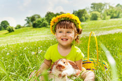 Smiling girl wearing flowers circlet and rabbit. Smiling girl with flowers circlet with rabbit in the basket sitting in the park in summer Stock Images