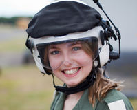 Smiling Girl Wearing Flying Helmet. Teenage girl modelling white military style flying helmet, with clear visor, wearing flying suit stock photography