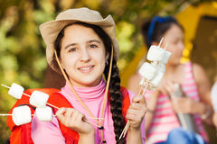 Smiling girl wearing hat holds marshmallow sticks Stock Photos