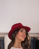 Smiling girl wearing red hat at store looking upwards Stock Images