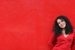 Smiling Girl Wearing Red On Red Wall Stock Photography