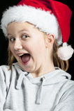 Smiling girl wearing a santa hat. A young happy girl wearing a christmas hat smiles Stock Photography