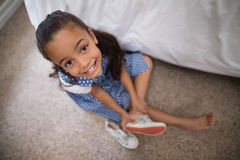 Smiling girl wearing shoe at home Royalty Free Stock Photography