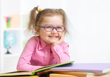 Smiling girl wearing spectacles reading book Royalty Free Stock Photo
