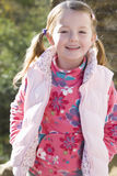 Smiling girl wearing vest outdoors Stock Images