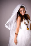 Smiling girl in wedding dress. A studio portrait of a happy, smiling young teenage girl in a white wedding dress Stock Photography