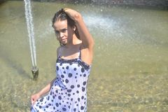 Smiling girl in a wet dress and wet hair posing in the water at the fountain Royalty Free Stock Photos