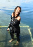 Smiling girl in wetsuit. Smiling tropical girl with tongue out - young indonesian woman dressed up into wetsuit for scuba diving making striptease in water Stock Photography