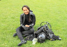 Smiling girl in wetsuit. Smiling tropical girl - young indonesian woman dressing up into wetsuit and getting ready bottle, BCD, jacket, regulator and gloves for Stock Image
