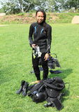 Smiling girl in wetsuit. Smiling tropical girl - young indonesian woman dressing up into wetsuit and getting ready bottle, BCD, jacket, regulator and mask for Stock Image