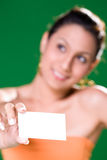 Smiling Girl with white card. Beautiful girl holding white card on green background smiling with card in focus Stock Photos