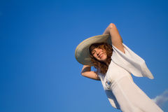 Smiling girl in white dress. On the blue sky Stock Images