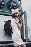 Smiling girl in white dress and fur hat in city Royalty Free Stock Photo