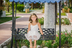 Smiling girl in white dress sitting on forged swin Stock Photography