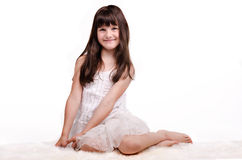 Smiling girl in white dress on white carpet Stock Photography