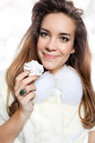 Smiling girl in white fur with meringue Royalty Free Stock Photo
